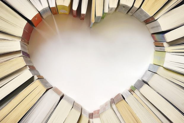 Books standing on table in shape of heart