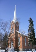 A brick church with a white steeple