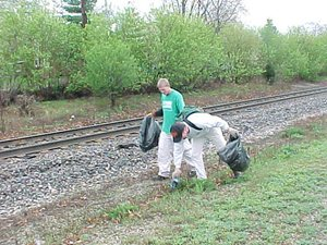 2 people picking up trash near a railroad track